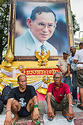 "11 MAY 2013 - BANGKOK, THAILAND:  Protesting farmers sit in front of a portrait of Bhumibol Adulyadej, the King of Thailand. Several hundred small scale family farmers camped out ""Government House"" (the office of the Prime Minister) in Bangkok to Thai Prime Minister Yingluck Shinawatra to deliver on her promises to improve the situation of family farmers. The People's Movement for a Just Society (P-move) is a network organization which aims strengthen the voices of different, but related causes working to bring justice for marginalized groups in Thailand, including land rights for small-scale farmers, citizenship for stateless persons, fair compensation for communities forced to relocate to accommodate large scale state projects, and housing solutions for urban slum dwellers, among others.   PHOTO BY JACK KURTZ"
