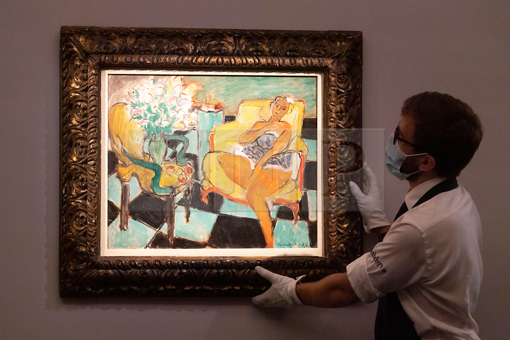 © Licensed to London News Pictures. 23/07/2020. London, UK.  A Sotheby's staff member holds a painting titled Danseuse assise dans un fauteuil (1942) by artist Henri Matisse with an estimate of £8-12 million. Works spanning over half a millennium of art history go on display at Sotheby's London ahead of a one-off auction on July 28. Titled 'Rembrandt to Richter', the sale will offer the very best from Old Masters, Impressionist & Modern Art, Modern & Post-War British Art and Contemporary Art – travelling from the Italian Renaissance through to Pop Art. Photo embargoed for usage until 24th July 2020 09:00. Photo credit: Ray Tang/LNP