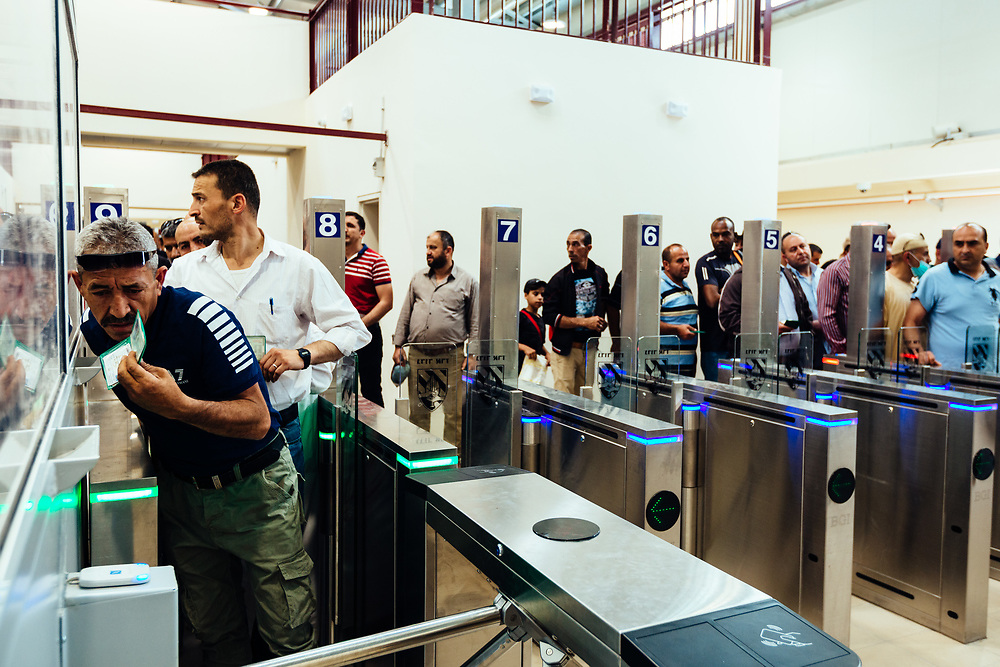 Palestinians use a biometric card at an automated gate equipped with a facial recognition system, as they cross Qalandiya checkpoint, south of Ramallah, West Bank, on May 17, 2019. The Palestinians on the left side of the photograph had to pass through an inspection booth, due to a problem with their new biometric card. Israeli authorities are introducing biometric border crossing systems at West Bank checkpoints, thus minimizing the interaction between Israeli soldiers and Palestinians crossing into Israel.