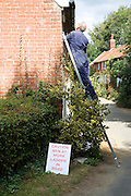 Man painting a house standing on a ladder with warning sign