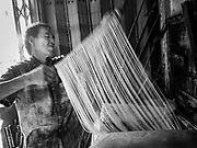 """29 DECEMBER 2018 - BANGKOK, THAILAND: A man stretches longevity noodles in his family shophouse. The family has been making traditional """"mee sua"""" noodles, also called """"longevity noodles"""" for three generations in their home in central Bangkok. They use a recipe brought to Thailand from China. Longevity noodles are thought to contribute to a long and healthy life and  are served on special occasions, especially Chinese New Year, which is February 4, 2019. These noodles were being made for Chinese New Year.       PHOTO BY JACK KURTZ"""