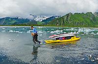 Man hauls SUPs and gear on a kayak up the feeder river to Bear Lake and Bear Glacier, Alaska.
