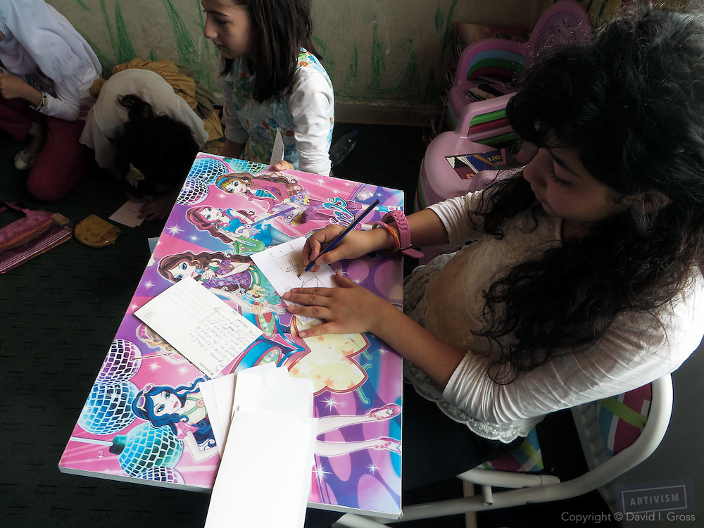 Syrian children in the al-Bashayer school paint pictures.