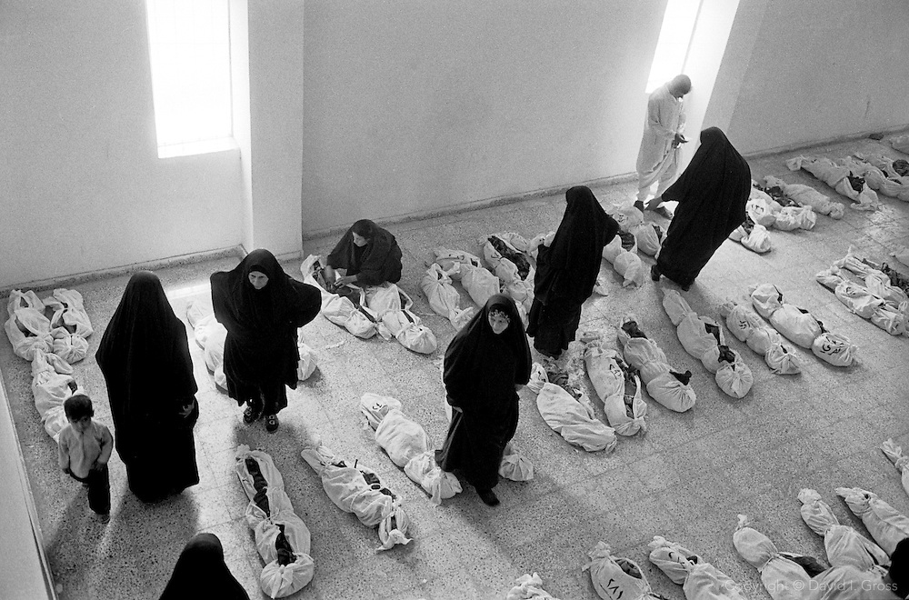 Bones in shrouds fill the gymnasium of the local sports center in Al-Musayab, Iraq, now the home of an Iraqi human rights organization which oversees the exhumations of bodies from local mass graves. People come from all over Iraq to check the clothing and ID cards of the bodies, hoping to discover a long-lost relative.