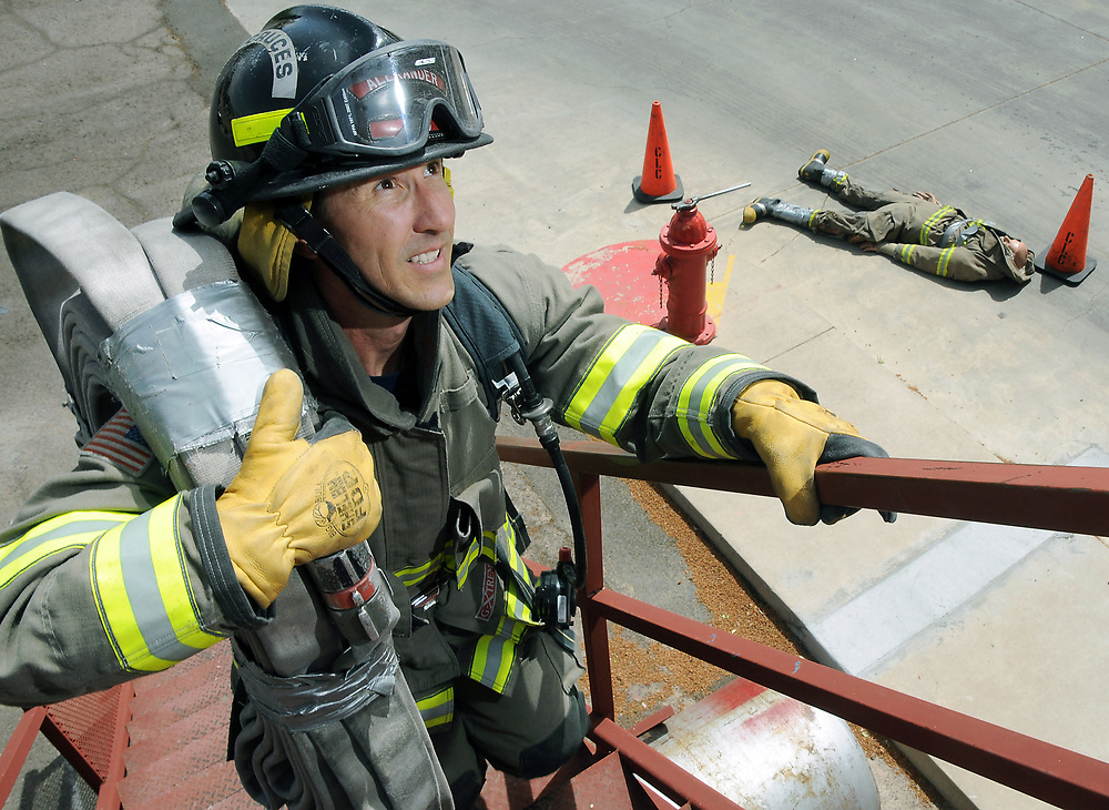 """Las Cruces firefighter Steve Alexander demonstrates a portion of the department's Physical Ability Test on Thursday, April 9, 2015, at Fire Station 4 located on Missouri Avenue. The annual test consists of nine job-simulated obstacles that must be completed in full bunker gear in less than eight minutes. Alexander completed his yearly test in March with a time of 4 minutes, 23 seconds. Pictured laying in the background is a mannequin that is used during the """"Dummy Drag"""" portion of the test."""