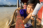 """17 JUNE 2013 - YANGON, MYANMAR:  A Burmese woman going to Dala on the Yangon-Dala Ferry. The ferry to Dala opposite Yangon on the Yangon River is the main form of transportation across the river. Every day the ferry moves tens of thousands of people across the river. Many working class Burmese live in Dala and work in Yangon. The ferry is also popular with tourists who want to experience the """"real"""" Myanmar. The rides takes about 15 minutes. Burmese pay about the equivalent of .06¢ US for a ticket.  Foreigners pay about the equivalent of about $4.50 US for the same ticket.   PHOTO BY JACK KURTZ"""