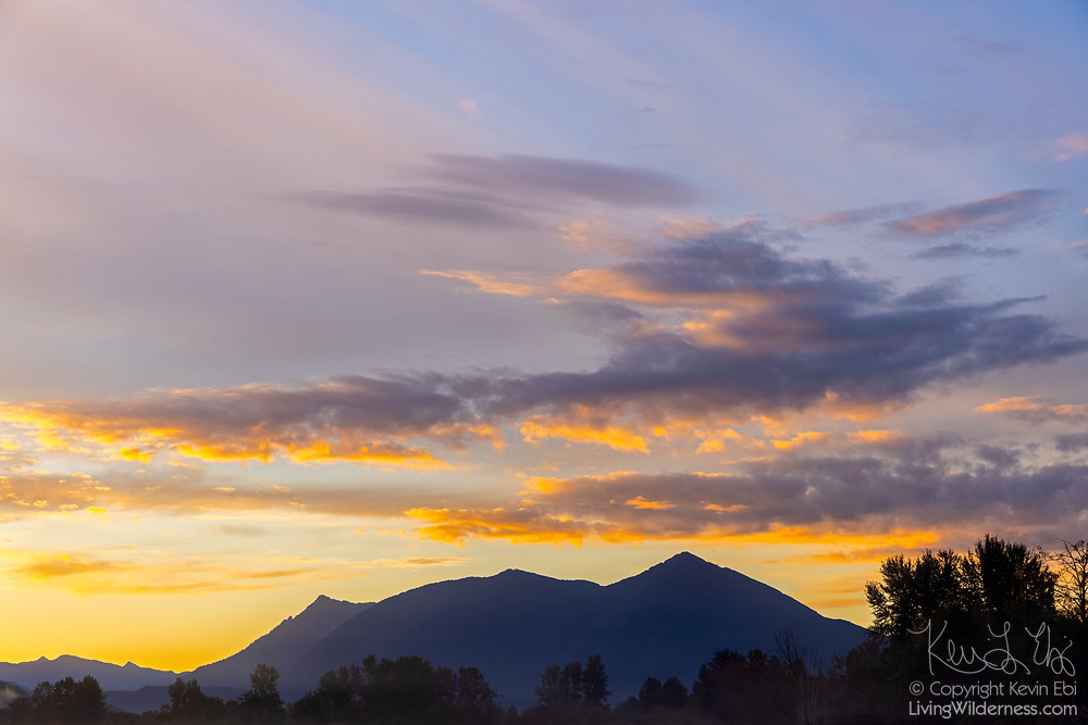 A fall sunrise colors the skies over several mountain peaks east of North Bend, Washington. In this image, the most prominent peaks are (from right to left) Mount Washington (4416 feet, 1346 meters), Change Peak (4321 feet, 1317 meters), and McClellan Butte (5108 feet, 1557 meters). The distant mountains on the left edge of the image are Abiel Peak (5321 feet, 1622 meters) and Silver Peak (5495 feet, 1675 meters). The mountains are located on the western edge of the Cascade Range.