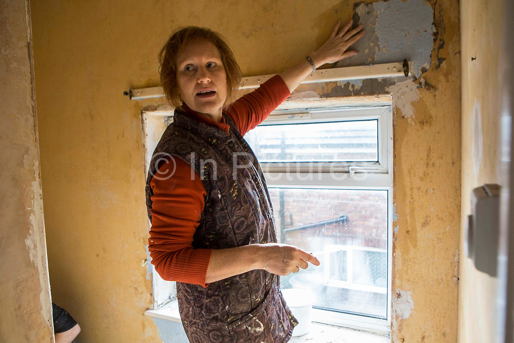 Young volunteers from Longton Community Church stripping wallpaper during the decoration process.  Local people can access the organisations redecoration scheme to improve living condition. Improving the lives of those in need in the local community, Leyland, Lancashire.