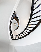 Looking up at architectural details of an ornate spiral staircase.