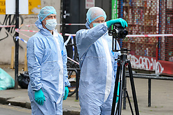 © Licensed to London News Pictures. 24/04/2019. London, UK. Forensic officers at the crime scene on Harlesden High Street, Brent in West London where a 21 year old man was stabbed on Tuesday 23 April 2019 at 9.07pm. According to the Met Police, the suspects arrived in two cars before blocking traffic in order to carry out the attack. The victim fled into a bookmakers (Paddy Power) to seek help before the arrival of emergency services. The victim was pronounced dead at a hospital at 2.47am on Wednesday 24 April 2019. Photo credit: Dinendra Haria/LNP