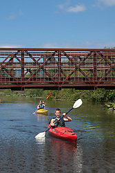 North America, United States, Washington, Bellevue, teenage boy and girl kayaking under bridge in Mercer Slough Nature Park.  MR
