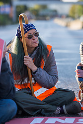 © Licensed to London News Pictures.  04/10/2021. London, UK. An activist from Insulate Britain is seen blocking the A12 Blackwell Tunnel Northern Approach in east London. Photo credit: Marcin Nowak/LNP