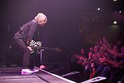 On stage during their show, Rick Parfitt of the band Status Quo stops playing his guitar and leans forward towards the enthusiastic audience in the front row at l'Aeronef in Lille, France during their 2007 European Tour. Parfitt and Francis Rossi are the two original members of the band, having met as school boys in the early 60s. Their distinctive three-chord guitar riff has made them a household name with hits like: Rockin' All Over the World and Sweet Caroline; selling 118 million albums. Over their 40 years of performing, QUO have played over 6000 live shows to an audience of 25 million people and travelling four million miles and spent 23 years away from home.