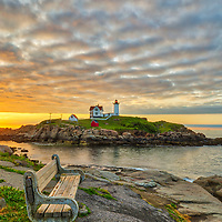 Nubble Lighthouse taken at sunrise in York, ME. Loved watching this sunrise and capturing a sun star of the rising sun while the first light created a beautiful sky across one of Maine's most scenic lighthouses, Nubble Light. Early morning is my favorite time of the day, when I can enjoy quietude and solitude.<br />