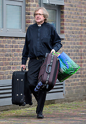© Licensed to London News Pictures. 24/06/2017. London, UK. A vicar carrying bags as residents are evacuated from the Burnham block on the Chalcots Estate in Camden after it failed a fire inspection because of combustable cladding. More than 700 flats in tower blocks on an estate in the Swiss Cottage area of north-west London are being evacuated because of fire safety concerns. Photo credit: Ben Cawthra/LNP