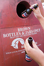 Hands putting brown glass bottles into a recycling bank,
