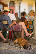 Man relaxing from walking his dog at a piano concert attended by the village in the medieval square, 19th July 2015, Lagrasse France.