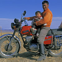 MONGOLIA, Darhad Valley. Herder & his son on his  motorcycle, a machine gradually replacing horses for distant travel
