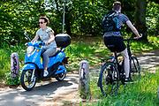 Een fietser moet door het gras uitwijken voor een scooter op een fietspad tussen Soest en Den Dolder door het bos.<br /> <br /> Cyclists ride a cycle path between Soest and Den Dolder in the woods.