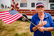 29 AUGUST 2020 - RUNNELLS, IOWA: A woman watches the hearse carrying the remain of Pvt Roy Brown Jr arrive at the funeral for Pvt. Brown's funeral in Runnells, IA. Pvt. Brown was a US Army soldier in World War II. He was an infantryman in the 126th Infantry Regiment, 32nd Infantry Division, serving in the Australian Territory of Papua (now Papua New Guinea). He went missing in action on Dec. 2, 1942. Unidentified remains were recovered on Feb. 2, 1943 and were eventually interred in the Manila American Cemetery. On May 14, 2019, Defense POW/MIA Accounting Agency using dental records, circumstantial evidence and DNA identified the remains as Pvt. Brown's. He was reinterred in the Lowman Cemetery in Runnells Saturday.      PHOTO BY JACK KURTZ