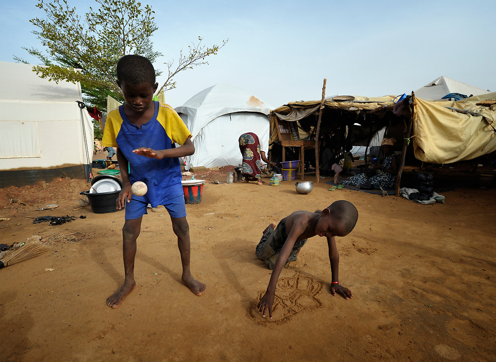 Children at play in a camp in Mopti, Mali, for families displaced by the fighting in the north of the country. Islamist rebels seized control of the north of Mali in 2012, but were chased out in early 2013 by French troops. Many displaced and refugee families have yet to return, preferring to wait for better security and improved economic conditions in the north.