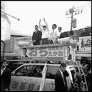 """Shinzo Abe (center) speaks at tokyo rally endorsing Local candidates for Office in the General election called by Korizumi's push to reform the Postal service.....An October 2005 government reshuffle saw him appointed as chief cabinet secretary, a key position sometimes referred to as the """"prime minister's wife"""".....His promotion was seen as a sign that Prime Minister Junichiro Koizumi may want Mr Abe to succeed him next Year,  when he is expected to step down."""