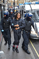 © Licensed to London News Pictures.  11/06/2013. LONDON, UK. Police officers escort an arrested arrested anti G8 protester to a waiting red London bus.  Photo credit: Cliff Hide/LNP