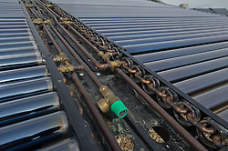 Solar water heating panels on the top of a building using a solar thermal collector. They are designed to follow the sun as it moves from east to west. UK