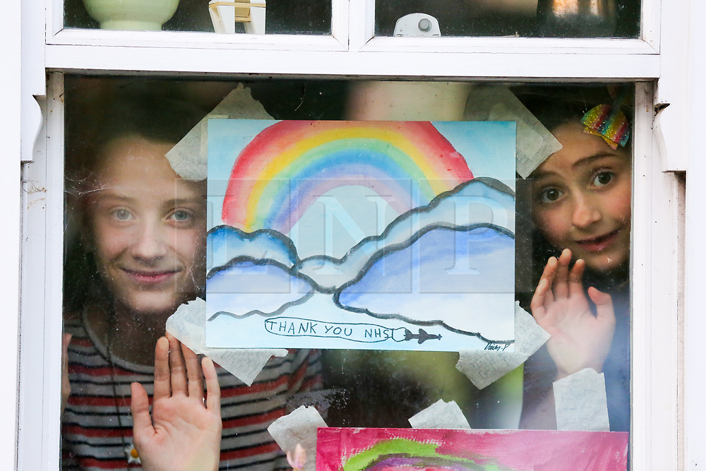 © Licensed to London News Pictures. 23/04/2020. London, UK. Children look out of the window next to their hand painted picture of a colourful rainbow displayed in a house in north London. Rainbows are used as a symbol of peace and hope. Photo credit: Dinendra Haria/LNP