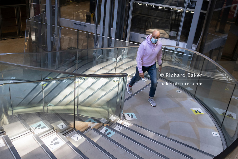 A man wearing a face covering climbs marked social distancing stairs in a shopping centre over the Easter weekend and during the third lockdown of the Coronavirus pandemic, in the City of London - the capital's financial district, on 4th April 2021, in London, England.