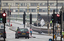 © Licensed to London News Pictures.23/03/2017.London, UK. A forensics officer is seen on Westminster Bridge near Parliament, the day after a lone terrorist killed 4 people and injured several more, in an attack using a car and a knife. The attacker managed to gain entry to the grounds of the Houses of Parliament, killing one police officer.Photo credit: Peter Macdiarmid/LNP