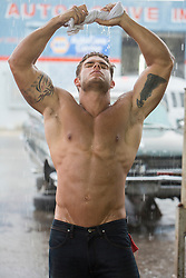 shirtless man in the rain wringing out his shirt above his head