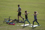 During the UKs governments Coronavirus continuing lockdown restrictions, when a total of 36,393 UK citizens are now reported to have lost their lives, a male runner passes two women practicing yoga in Ruskin Park, a public green space in the south London borough of Lambeth, on 22nd May 2020, in London, England.