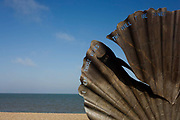 "Scallop, a 4 metre high steel sculpture of two interlocking scallop shells on Aldeburgh beach dedicated to Benjamin Britten. Hambling's Scallop (2003) stands on the north end of Aldeburgh beach. It is a tribute to Benjamin Britten and is pierced with the words ""I hear those voices that will not be drowned"" from his opera Peter Grimes. Aldeburgh is a coastal town in Suffolk, East Anglia, England. Located on the River Alde, the town is notable for its internationally renowned Aldeburgh Festival of arts, which takes place at nearby Snape Maltings, was created in 1948 by the resident and acclaimed composer Benjamin Britten. The Blue Flag shingle beach and fisherman huts is where freshly caught fish are sold daily."