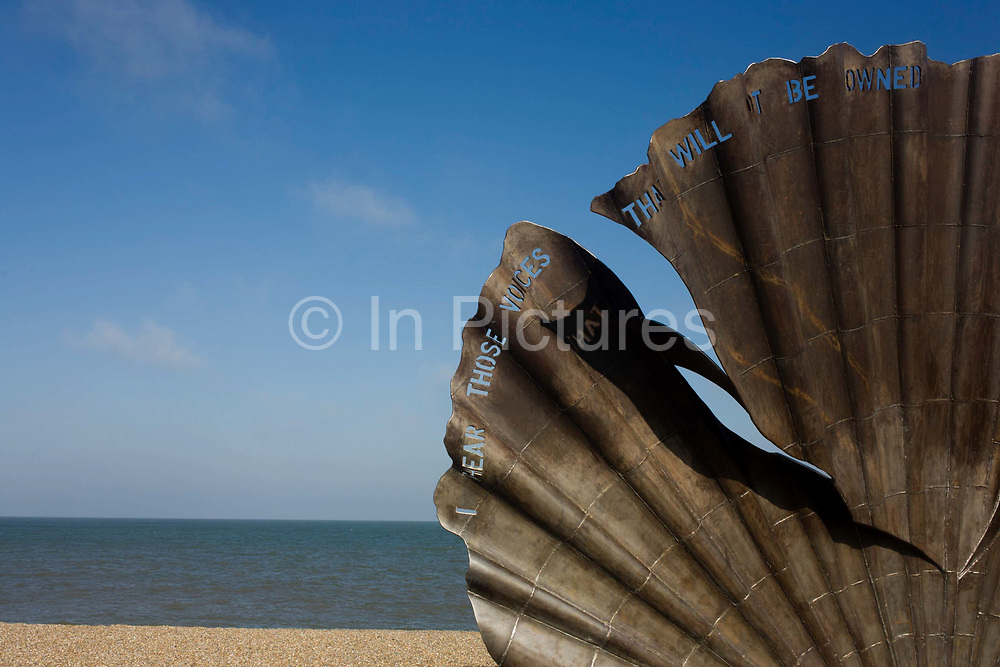 """Scallop, a 4 metre high steel sculpture of two interlocking scallop shells on Aldeburgh beach dedicated to Benjamin Britten. Hambling's Scallop (2003) stands on the north end of Aldeburgh beach. It is a tribute to Benjamin Britten and is pierced with the words """"I hear those voices that will not be drowned"""" from his opera Peter Grimes. Aldeburgh is a coastal town in Suffolk, East Anglia, England. Located on the River Alde, the town is notable for its internationally renowned Aldeburgh Festival of arts, which takes place at nearby Snape Maltings, was created in 1948 by the resident and acclaimed composer Benjamin Britten. The Blue Flag shingle beach and fisherman huts is where freshly caught fish are sold daily."""