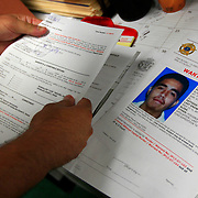 A mug shot of 18-year-old Gabriel Hernandez is seen as Investigator Mike Lopez looks over an arrest warrant for the Hernandez in the murder of Luis Fernando Lara at the Hidalgo County Sheriff's office. Several witnesses at La Puerta Negra bar identified Hernandez in the shooting, and that Lara was Hernandez' cousin.<br /> Nathan Lambrecht/The Monitor