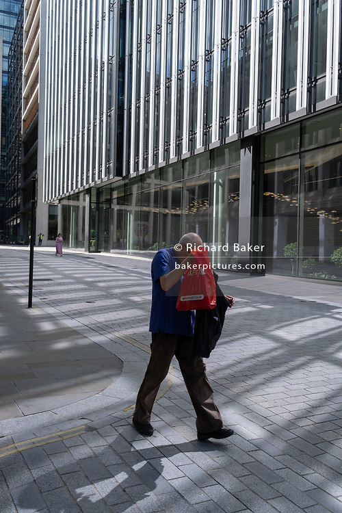 A man searches his jacket while walking down a street with reflected light from plate glass windows in the City of London, the capital's financial district which is still largely quiet as workers continue to work from home during the on-going Coronavirus pandemic,  on 6th August 2020, in London, England.