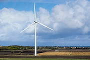 Truck on road shows great height of a wind turbine in the landscape  near Vix in the Loire Valley, France
