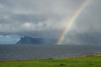 Rainbow passes before mountains peaks as summer storm approaches, Vestvågøy, Lofoten Islands, Norway