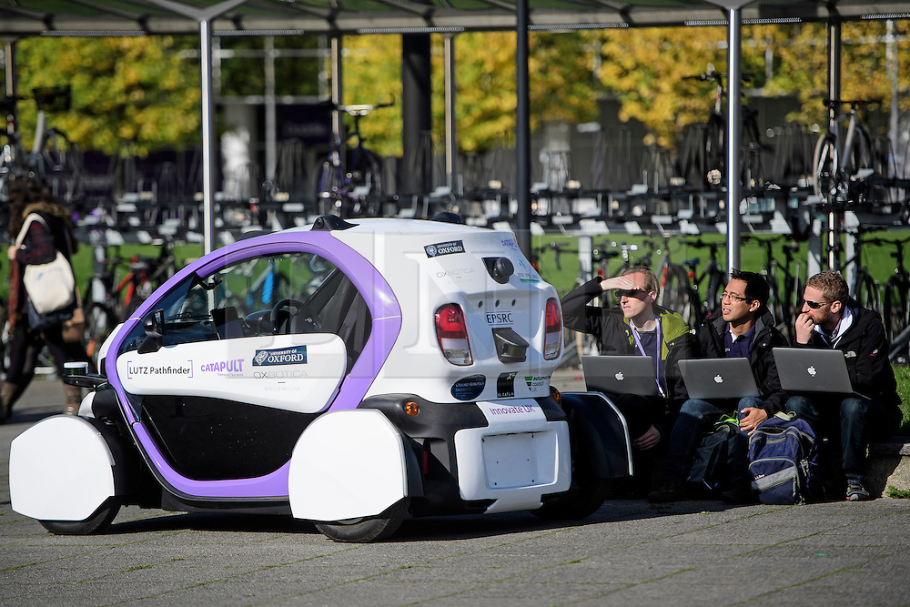 © London News Pictures. 11/10/2016. Milton Keynes, UK. Three technicians using laptops look on during testing of a driverless car around pedestrian areas in Milton Keynes in the first public test of autonomous electric vehicles in the UK. The vehicles have been developed by the Oxford Robotics Institute and Oxbotica. Photo credit: Ben Cawthra/LNP