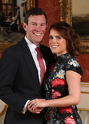 ALTERNATE CROP<br /> Princess Eugenie and Jack Brooksbank in the Picture Gallery at Buckingham Palace in London after they announced their engagement. Princess Eugenie wears a dress by Erdem, shoes by Jimmy Choo and a ring containing a padparadscha sapphire surrounded by diamonds.