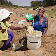 Two women drink from a hole dug into a dried riverbed in drought-hit Masking Province, Zimbabwe.  <br /> <br /> Untreated and untested, the shallow stagnant water is a potential source of pollutants and water-borne diseases. <br /> <br /> Drought in southern Africa is devastating communities in Zimbabwe, leaving 4 million people urgently in need of food aid. The government declared a state of emergency,. <br /> <br /> Here in Masvingo Province, the country's hardest hit province, vegetation has wilted, livestock is dying, and people are at serious risk of famine. <br /> <br /> Pictures shot by Justin Jin