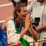 TOKYO, JAPAN August 1:  An emotional  Gianmarco Tamberi of Italy reacts after winning the gold medley jointly with Mutaz Essa Barshim of Qatar in the high jump for men during the Track and Field competition at the Olympic Stadium  at the Tokyo 2020 Summer Olympic Games on July 31, 2021 in Tokyo, Japan. (Photo by Tim Clayton/Corbis via Getty Images)
