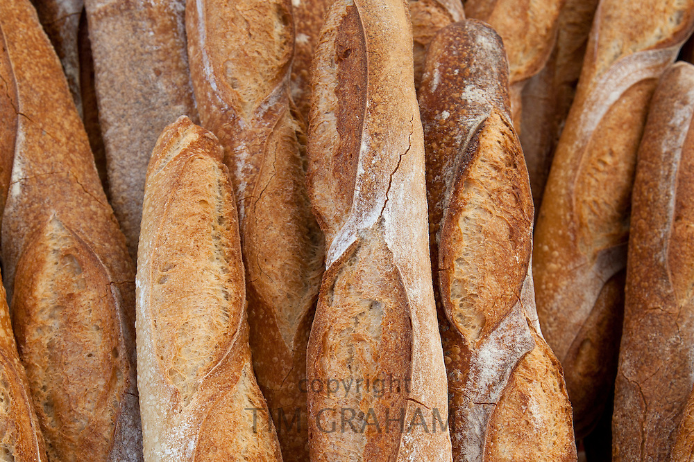 Freshly-baked French bread baguettes on sale at food market in Bordeaux region of France