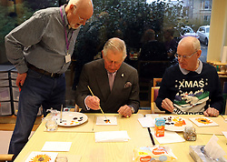 Prince Charles (known as The Duke of Rothesay when in Scotland, centre) taking part in a painting class during his visit to the Ayrshire Hospice in Ayr where he met patients and their families, staff and volunteers, with standing-volunteer occupational therapist George Bell (left) and patient Jim Fitzsimmons (right).