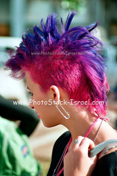A girl with purple, red and blue hair with a safety pin as an earring