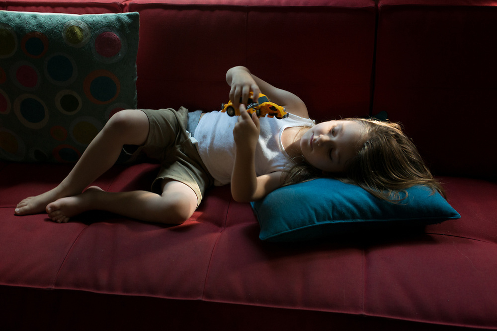 """Theodore lying on our red couch, playing with """"Bumble Bee, one of his Transformer vehicles, in soft light."""
