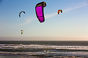 Kite surfers out in waves in afternoon sunshine on California coast near Big Sur