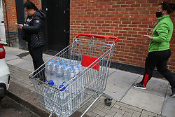 © Licensed to London News Pictures. 07/10/2020. London, UK. A shopper with cases of drinking water bottles in a shopping trolley as homes in East London are still without water following a water main pipe burst in Hackney Marshes on Tuesday. Photo credit: Dinendra Haria/LNP
