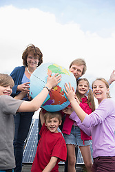 Mother father four kids playing with globe balloon
